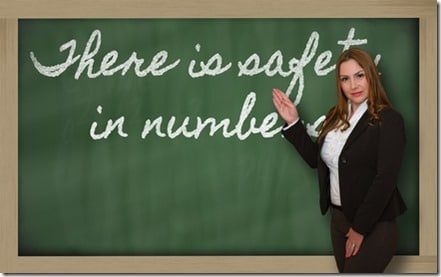 Teacher showing There is safety in numbers on blackboard