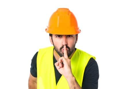 Workman making silence gesture over isolated white background